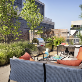 Terrace includes BBQ grilling stations and lush landscaping.