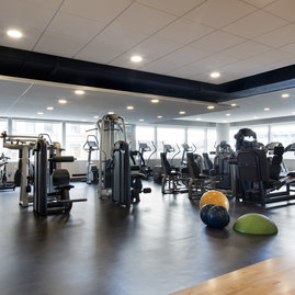 A state-of-the art Health and Fitness Center features cardio and strength equipment and lots of natural light streaming through a wall of windows.