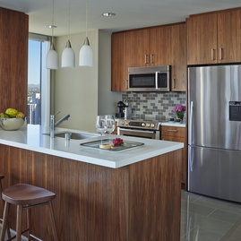 Gourmet kitchens showcase rich walnut cabinetry and Caesarstone counters.