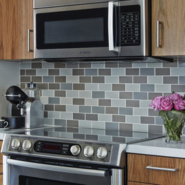 Full-height, tiled backsplashes elevate the well-designed kitchens.