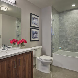 The lavish baths in The Emerson's apartments feature a marble counter and tub surround, walnut vanity with a Toto undermount sink, chrome fixtures and a mirrored medicine cabinet for additional storage.