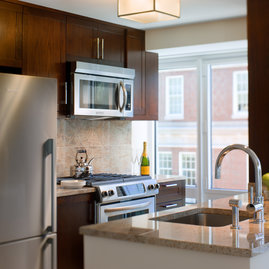 Custom gourmet kitchens feature granite countertops with stainless KitchenAid appliances and gas stoves.