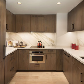 Gourmet kitchens include soft-close wood cabinetry and stainless steel appliances.