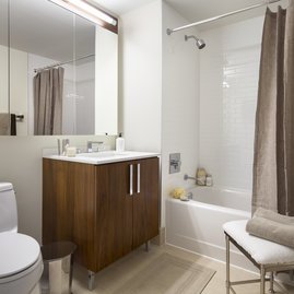 Luxurious white-tiled baths feature custom wood cabinetry and oversized custom-designed medicine cabinets.
