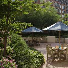 The meticulously landscaped garden patio includes outdoor dining space with barbeques for residents.