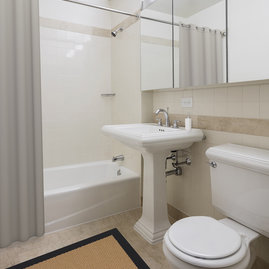 Classic marble bathrooms feature Kohler fixtures and storage-friendly oversized medicine cabinets.