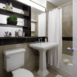 Lavish marble bathrooms with pedestal sinks complement the living spaces in these NYC luxury apartments.