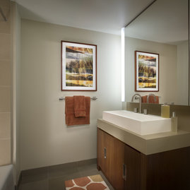 Bathrooms feature golden sandstone tile with arctic white corian vessel sinks.