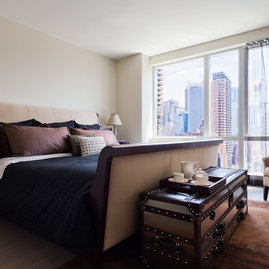 See the city lights from your bed with floor-to-ceiling windows in the bedroom.