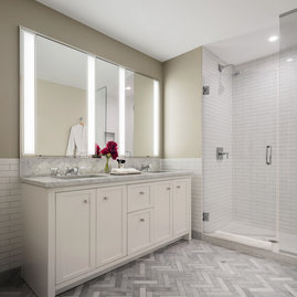 Luxuriate in master baths featuring white natural stone vanity, Kohler fixtures and accessories in polished chrome, and natural stone tile floor in white herringbone tile.