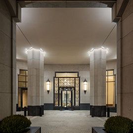 Dedicated residential entrance marked by a classic limestone-clad porte cochere.