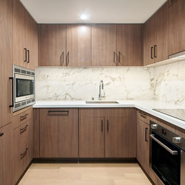 White quartz counters and Calacutta marble backsplash, soft-close wood cabinetry, stainless steel sink and premium stainless steel appliances with integrated wood paneling.