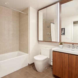 Luxurious bathrooms feature a walnut vanity, white quartz counters, and a mirrored medicine cabinet with integrated lighting