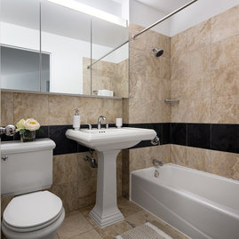 Elegant marble bathrooms with pedestal sinks and deep shelving.