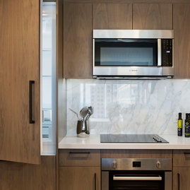 Kitchens feature Quartz countertops and Calcutta marble backsplashes.