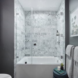 Luxe bathrooms include marble tub surround.