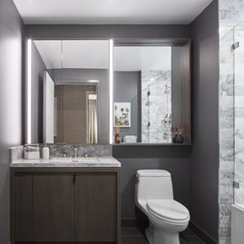 Luxe bathrooms include grey-oak vanities with marble counters, custom medicine cabinets and marble tub surround.