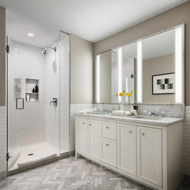 Master baths featuring white natural stone vanities, Kohler fixtures, and natural stone tile floors.