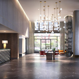 Flooded with natural light, the double-height lobby features an incredible 19-foot Calacatta Cielo stone fireplace and Pietra Grey marble floor.