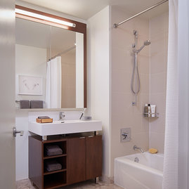 Custom bathrooms with polished natural stone floors, custom walnut vanities, and oversized showers.