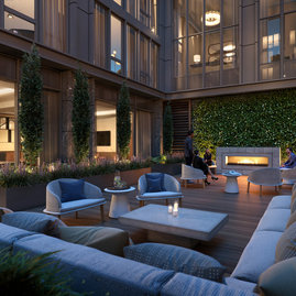 The landscaped courtyard seamlessly integrates the indoors and outdoors with comfortable seating before a fireplace.
