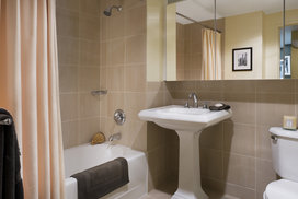 The lavish baths at The Paramount feature a pedestal sink and Italian tile walls and floors.