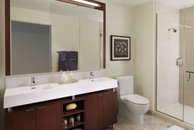 Custom bathrooms with polished natural stone floors, custom walnut vanities, and oversized showers