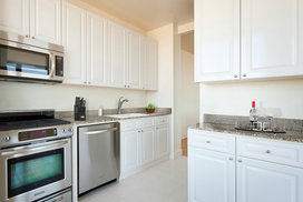 Layouts feature gourmet kitchens with paneled white cabinet doors, stainless steel appliances and granite counters.