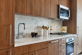 White quartz kitchen counter with a full-height Carrara marble tile backsplash