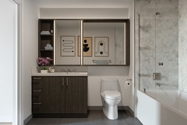 Bathrooms contain European-style oak vanity with white quartz counters, glass-enclosed shower/tub combination with marble tile surround, and custom medicine cabinet with integrated lighting.