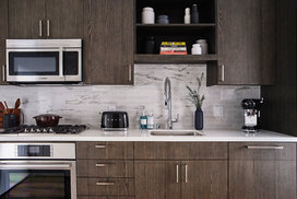 Gourmet kitchens feature gas cooktops and Bosch appliances with quartz counters and a marble backsplash.