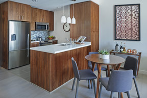 Aspire to culinary greatness in The Emerson's open kitchen with breakfast bar, featuring professional stainless steel appliances from Fisher & Paykel and Bosch, set against walnut cabinetry with Caesarstone counters and a full-height, tiled backsplash.